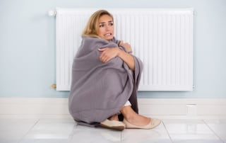 Young Cold Woman Wrapped In Blanket Sitting Near Heater At Home