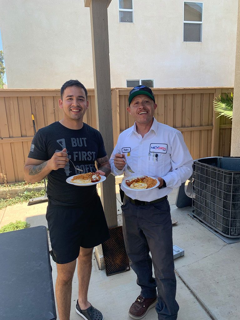 two people with plates of food in front of an open AC unit