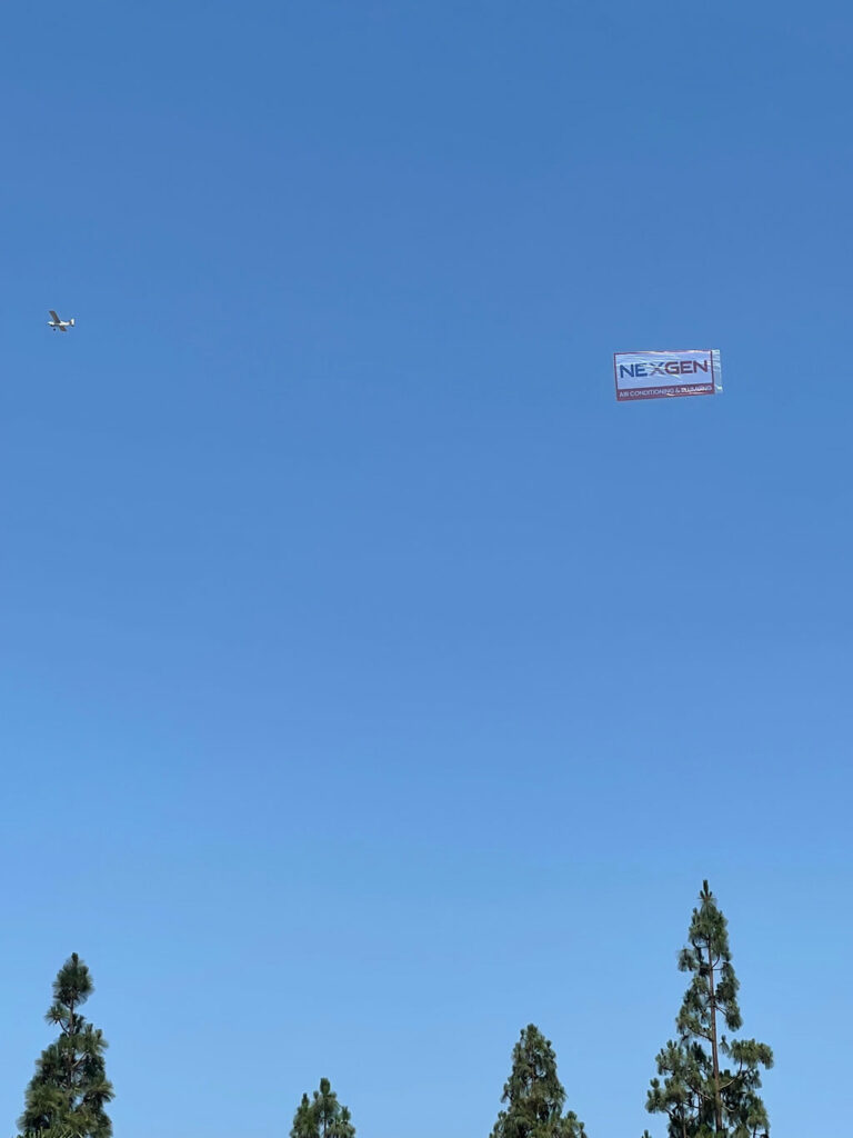 a clear blue sky with a nexgen banner and an airplane