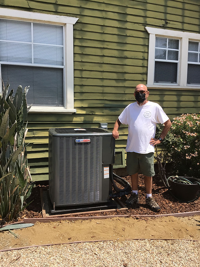 satisfied customer in front of new ac unit